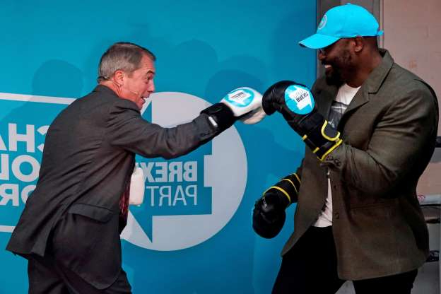 Slide 12 of 31: Brexit Party leader Nigel Farage (R) wears boxing gloves as he poses with British boxer Dereck Chisora, during his visit to Gator ABC Boxing Club in Ilford, east London on November 13, 2019, during a general election campaign visit. - Britain will go to the polls on December 12 to vote in a pre-Christmas general election. (Photo by Niklas HALLE'N / AFP) (Photo by NIKLAS HALLE'N/AFP via Getty Images)