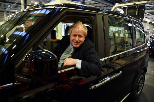 Slide 15 of 31: Britain's Prime Minister Boris Johnson sits in an electric taxi during his Conservative party general election campaign visit to the London Electric Vehicle Company (LEVC) in Coventry, central England on November 13, 2019. - Britain goes to the polls on December 12 to vote in a pre-Christmas general election. (Photo by Ben STANSALL / various sources / AFP) (Photo by BEN STANSALL/AFP via Getty Images)