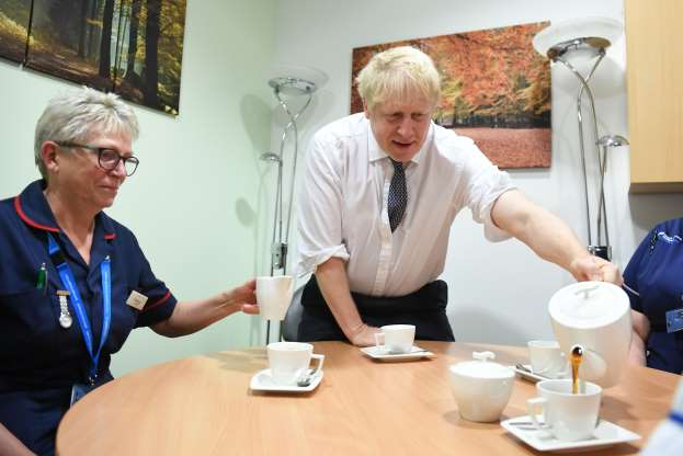 Slide 22 of 31: Prime Minister Boris Johnson pours tea as he meets staff and nurses during a visit to King's Mill Hospital in Sutton-in-Ashfield, while on the General Election campaign trail around the country. (Photo by Stefan Rousseau/PA Images via Getty Images)