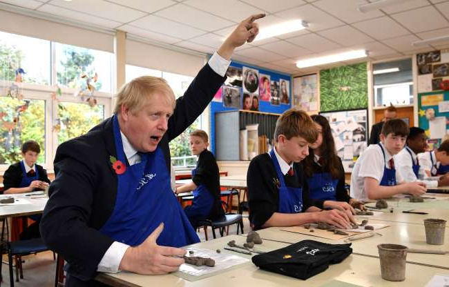 Slide 23 of 31: STAPLEFORD, ENGLAND - NOVEMBER 08: Prime Minister Boris Johnson participates in a school art lesson making clay figures, as he talks with school teachers during a general election campaign visit to George Spencer Academy on November 8, 2019 in Stapleford, near Nottinghamshire, United Kingdom. (Photo by Daniel Leal-Olivas - WPA Pool/Getty Images)