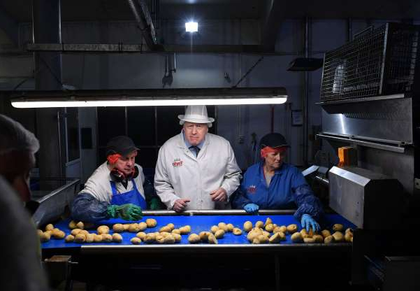 Slide 26 of 31: Britain's Prime Minister Boris Johnson (C) helps quality control workers during a general election campaign visit to the Tayto Castle crisp factory in County Armagh, Northern Ireland, on November 7, 2019. - Britain's two main parties promised billions of pounds of investment for hospitals, schools and infrastructure on Thursday as they seek to woo voters weary of austerity ahead of the December 12 general election. (Photo by Daniel LEAL-OLIVAS / POOL / AFP) (Photo by DANIEL LEAL-OLIVAS/POOL/AFP via Getty Images)
