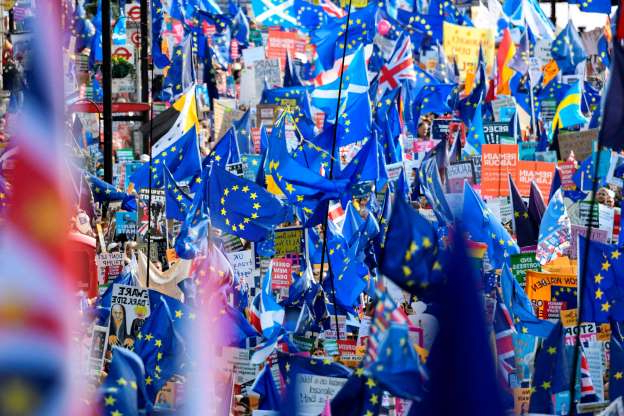 Slide 4 of 60: Demonstrators hold placards and EU and Union flags as they take part in a march by the People's Vote organisation in central London on October 19, 2019, calling for a final say in a second referendum on Brexit. - Thousands of people march to parliament calling for a
