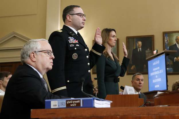 Slide 43 of 56: Jennifer Williams, an aide to Vice President Mike Pence, and National Security Council aide Lt. Col. Alexander Vindman, are sworn in before they testify before the House Intelligence Committee on Capitol Hill in Washington, Tuesday, Nov. 19, 2019, during a public impeachment hearing of President Donald Trump's efforts to tie U.S. aid for Ukraine to investigations of his political opponents. Attorney Michael Volkov is seated, right. (AP Photo/Alex Brandon)