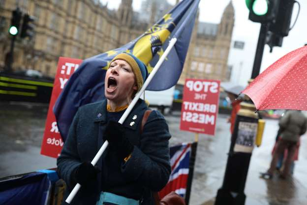 "Slide 50 of 60: LONDON, ENGLAND - MARCH 12:  Anti Brexit demonstrators protest in the rain ahead of the meaningful vote in Parliament on March 12, 2019 in London, England. MPs, who rejected Theresa May's Brexit deal earlier this year by a majority of 230, are due to vote on revised proposals after Theresa May secured last-minute ""legally binding"" changes, wanted to ensure the UK couldn't be indefinitely tied to the Irish backstop and a permanent customs union. (Photo by Dan Kitwood/Getty Images)"
