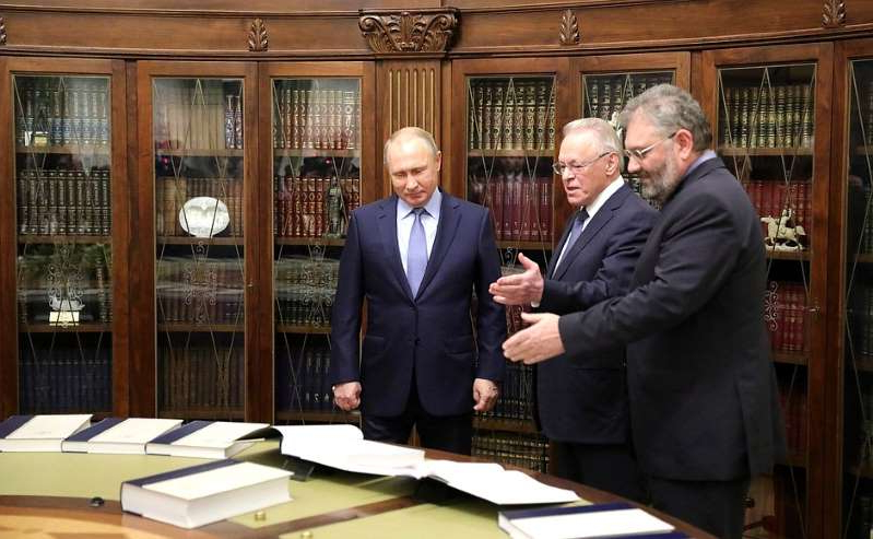 Yury Osipov, Vladimir Putin are posing for a picture: Great Russian Encyclopedia Sergei Kravets (L) and Russian Academy of Sciences member Yury Osipov present to Russian President Vladimir Putin (C) the complete edition of the Great Russian Encyclopedia at the Kremlin, Moscow, December 20, 2017.