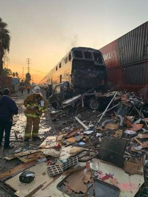 a group of people standing next to a train: A view of a Los Angeles commuter train that crashed into a vehicle on the tracks in Santa Fe Springs