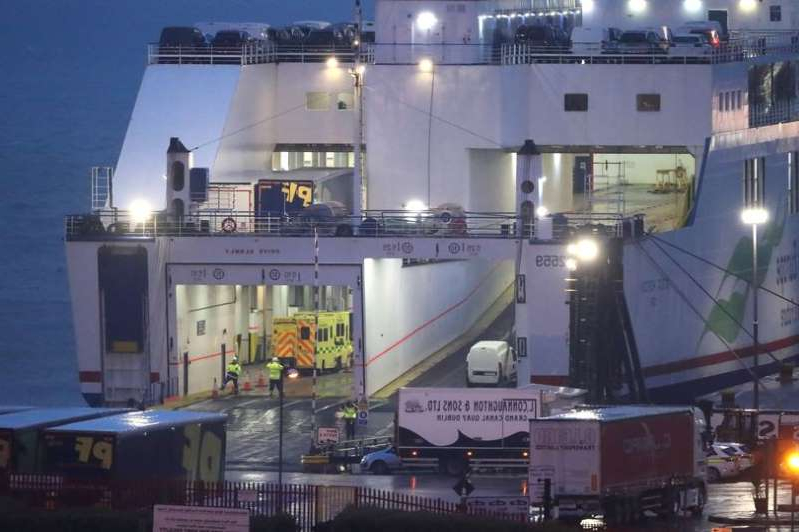 a large ship in the background: Emergency personnel at Rosslare Europort in Co Wexford, board the Stena Line ferry after 16 people were discovered in a sealed trailer on the ship sailing from France