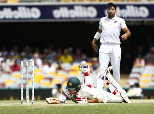 a man with a football ball: Australia's Joe Burns, front, falls after slipping in his crease as Pakistan's Imran Khan, back, watches on during their cricket test match in Brisbane, Australia, Friday, Nov. 22, 2019. (AP Photo/Tertius Pickard)
