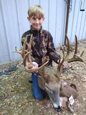 a young boy standing in front of a deer: Kaden Sheat, 14, killed his biggest deer yet - a 22-point buck - during this year's youth hunt.