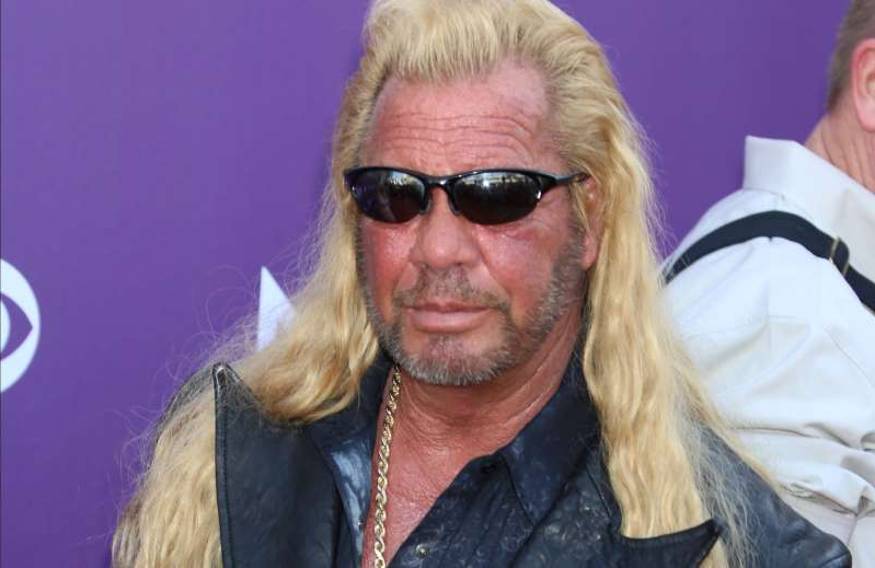 Duane 'Dog' Chapman wearing glasses and smiling at the camera