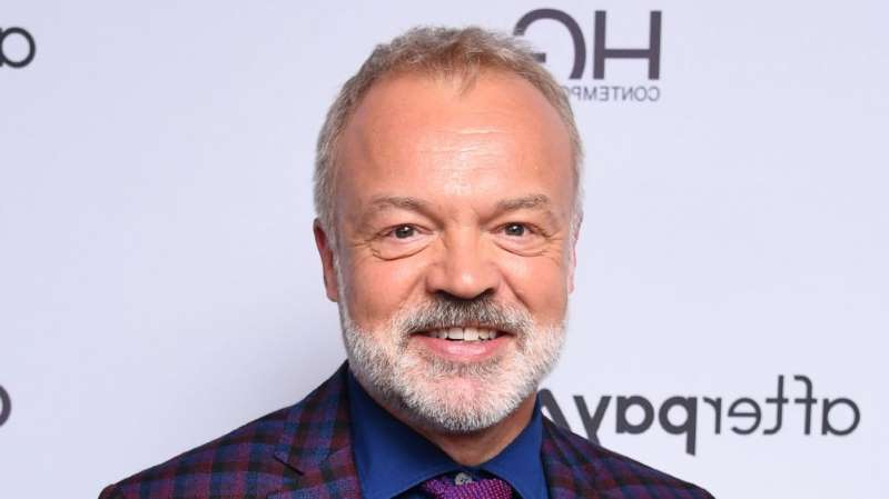 Graham Norton wearing a suit and tie smiling at the camera