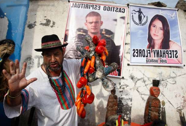 Joran van der Sloot holding a sign: A shaman performs a ritual for the spiritual punishment of Joran van der Sloot, in poster top center, and for justice for Stephany Flores, in poster at left, in Lima, Peru, Jan. 6, 2012.