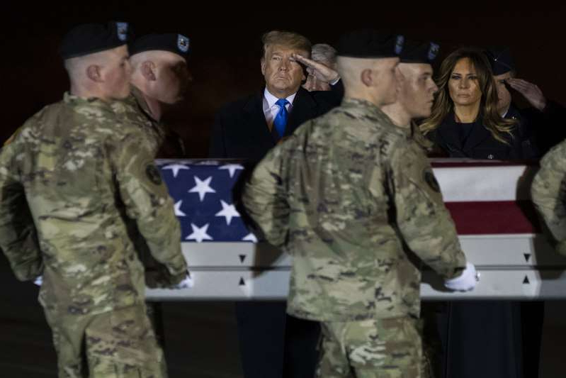 President Donald Trump and first lady Melania Trump look on as a U.S. Army carry team moves a transfer case containing the remains of Chief Warrant Officer 2 David C. Knadle, of Tarrant, Texas, who according to the Department of Defense died in Afghanistan, during a casualty return ceremony, Thursday, Nov. 21, 2019, in Dover Air Force Base, Del. (AP Photo/ Evan Vucci)