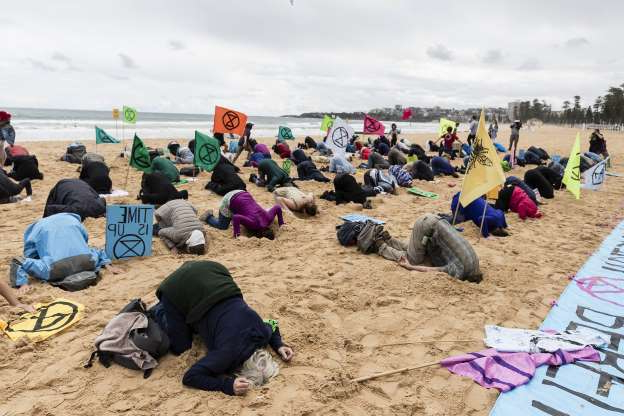 Slide 11 of 50: SYDNEY, AUSTRALIA - OCTOBER 11: Activists bury their heads in the sand on Manly Beach on October 11, 2019 in Sydney, Australia. The event was organised as part of Extinction Rebellion's global