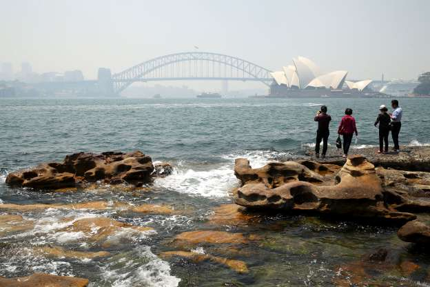 Slide 15 of 31: SYDNEY, AUSTRALIA - NOVEMBER 19: Vistors at Mrs Macquarie's Chair overlook a smoke covered Sydney Harbour on November 19, 2019 in Sydney, Australia. NSW remains under severe or very high fire danger warnings as more than 50 fires continue to burn across the state. Six lives and 530 homes have been lost since NSW bushfire season hit, with more than 420 homes destroyed in the past fortnight alone. (Photo by Mark Kolbe/Getty Images)