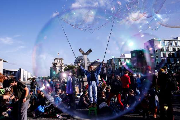Slide 20 of 50: BERLIN, GERMANY - OCTOBER 09 : A member of Extinction Rebellion, a group of environmentalist activists, makes bubbles as protests continue in order to draw attention to climate change and global warming in Berlin, on October 9, 2019. - Extinction Rebellion activists began gathering in cities around the world on October 7 to kick off a fortnight of global civil disobedience demanding governments take urgent action on climate change. Protesters gathered at various points of the city and blocked traffic at Marshall-Bridge. (Photo by Abdulhamid Hosbas/Anadolu Agency via Getty Images)