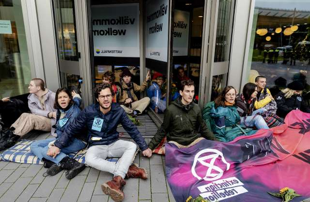 Slide 22 of 50: Mandatory Credit: Photo by ROBIN VAN LONKHUIJSEN/EPA-EFE/Shutterstock (10439101c) Climate activists from the Extinction Rebellion action glue themselves to the entrance door of the Vattenfall (formerly Nuon) head office near Amsterdam Bijlmer Arena in Amsterdam, the Netherlands, 08 October 2019, where they want to set up a so-called climate camp and prepare new actions. The global environmental movement Extinction Rebellion announced worldwide climate change protests and blockades for two weeks starting 07 October. Climate activists at Vattenfall  headquarters, Amsterdam, Netherlands - 08 Oct 2019