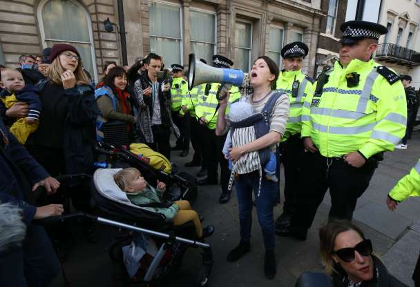 Slide 23 of 50: Lorna Greenwood speaks to protesters as the police block Whitehall, preventing the Extinction Rebellion mass 'nurse-in' reaching Downing Street in Westminster, London. (Photo by Jonathan Brady/PA Images via Getty Images)