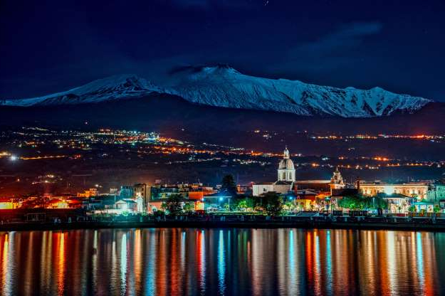 Slide 24 of 31: CATANIA, ITALY - NOVEMBER 15: A snow-capped Mount Etna is seen from the port of Riposto on November 15, 2019 in Catania, Italy. The volcano is currently emitting a slight emission of ash from the summit craters, in particular craters of NE and Voragine. The average amplitude of the volcanic tremor is maintaining average values. (Photo by Fabrizio Villa/Getty Images)
