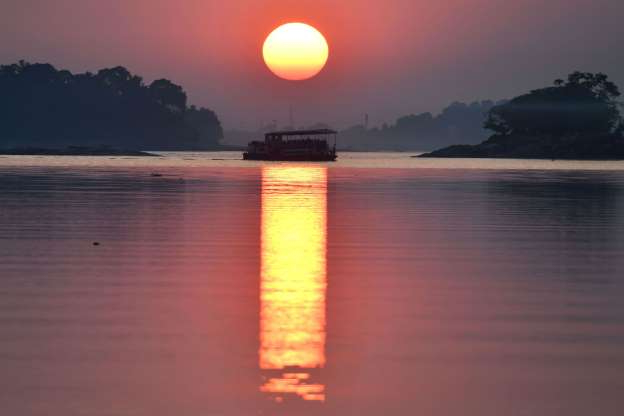 Slide 25 of 31: A ferry travels along the river Brahmaputra during sunset in Guwahati on November 15, 2019. (Photo by Biju BORO / AFP) (Photo by BIJU BORO/AFP via Getty Images)