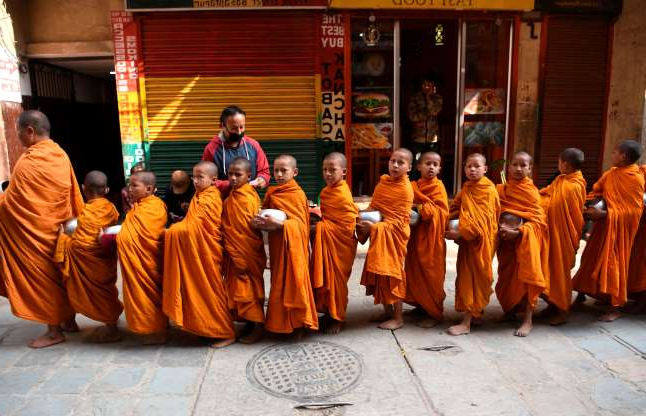 Slide 29 of 31: Nepali Buddhist monks hold metal alms pots as they march through an alley near Durbar Square in Kathmandu on November 20, 2019. (Photo by PRAKASH MATHEMA / AFP) (Photo by PRAKASH MATHEMA/AFP via Getty Images)