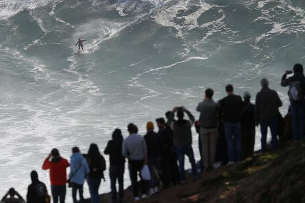 Slide 30 of 31: People on top of a cliff watch as a surfer rides a wave during a big wave surfing session at the Praia do Norte, or North beach, in Nazare, Portugal, Wednesday, Nov. 20, 2019. (AP Photo/Armando Franca)