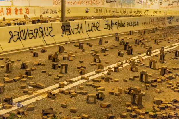 Slide 5 of 31: HONG KONG, CHINA - NOVEMBER 18: Protesters use bricks to barricade near Hong Kong Polytechnic University in the Tsim Sha Tsui district on November 18, 2019 in Hong Kong, China. Anti-government protesters organized a general strike since Monday as demonstrations in Hong Kong stretched into its sixth month with demands for an independent inquiry into police brutality, the retraction of the word