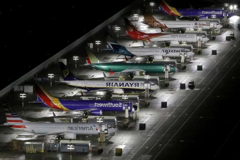 a large airplane at an airport: FILE PHOTO: Aerial photos show Boeing 737 Max airplanes on the tarmac in Seattle