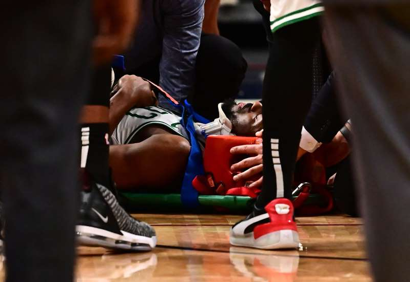 a person sitting on a table: Kemba Walker leaves the floor on astretcher.