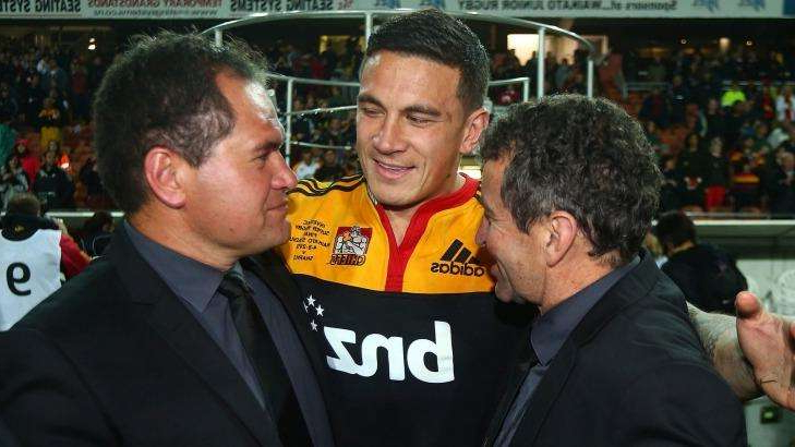 Sonny Bill Williams standing in front of a crowd: Wayne Smith (left), Sonny Bill Williams (centre) and Dave Rennie (right) celebrate after the Chiefs won the Super Rugby title in 2012.