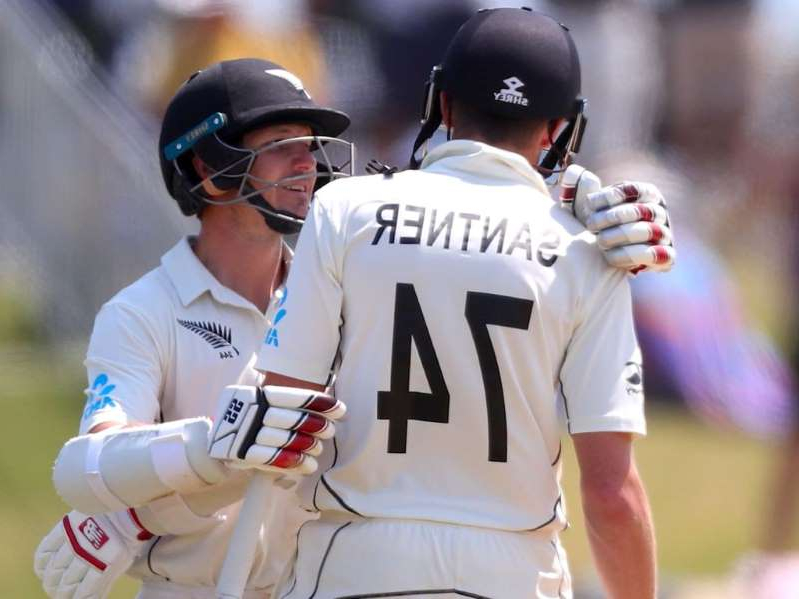 a baseball player holding a bat: Santer is embraced by BJ Watling after reaching his century