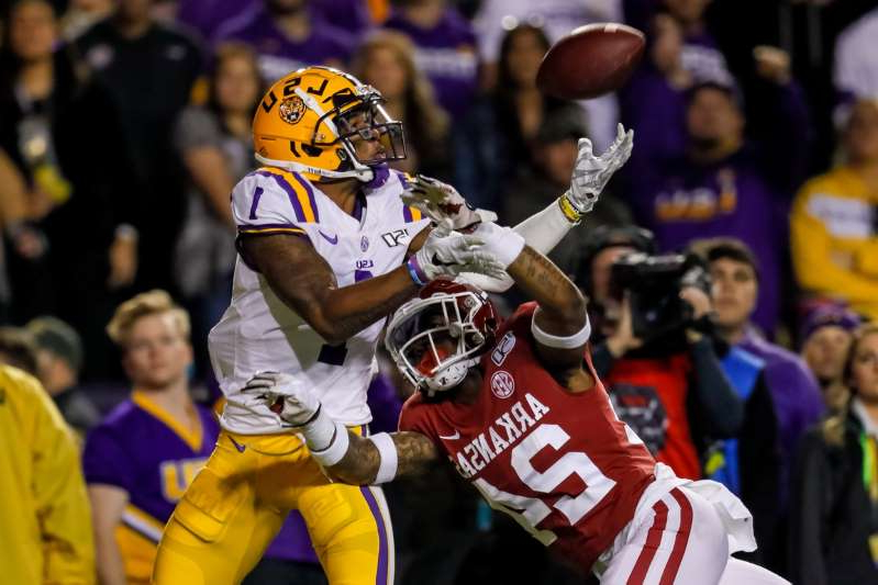 a crowd of people watching a baseball game: LSU Tigers wide receiver Ja'Marr Chase (1) catchers a touchdown pass over Arkansas Razorbacks defensive back LaDarrius Bishop (24) during the first half at Tiger Stadium on November 23, 2019.
