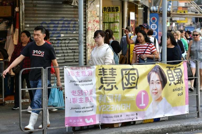 a group of people walking down a street: The district council polls normally stir little excitement but with protests roughing up the city, pro-democracy candidates are hoping to make a statement