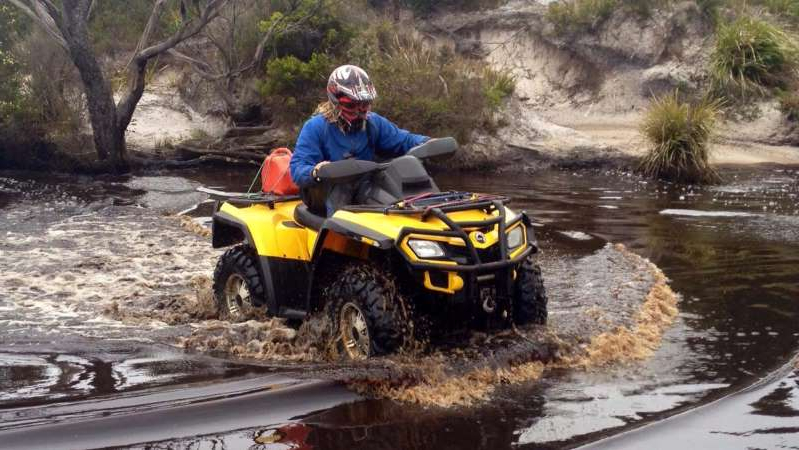 a man riding a motorcycle down a river: The woman who died at Stanley was riding a quad bike. (ABC News: Emily Bryan)