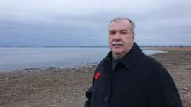 a man standing next to a body of water: Kenneth McGee was a constable in the Chatham police force while serial killer Allan Legere was at large in what is now Miramichi.