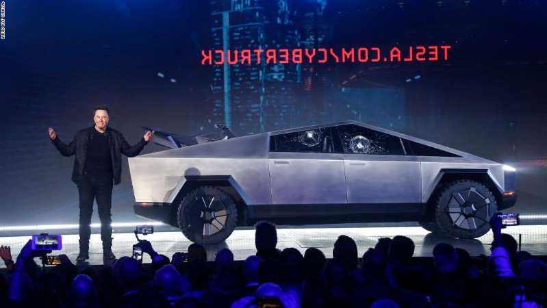 a man standing on a stage: Tesla CEO Elon Musk introduces the Cybertruck at Tesla's design studio Thursday, Nov. 21, 2019, in Hawthorne, Calif. Musk is taking on the workhorse heavy pickup truck market with his latest electric vehicle. (AP Photo/Ringo H.W. Chiu)