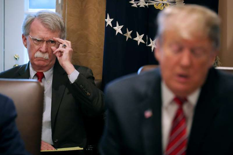 John R. Bolton wearing a suit and tie talking on a cell phone: President Donald Trump and then-National Security Adviser John Bolton in February.