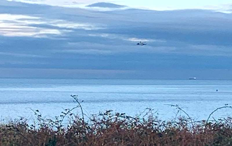 a bird flying over a body of water: A Coastguard helicopter off the North Wales coast near Anglesey (NWP Anglesey/Facebook/PA)