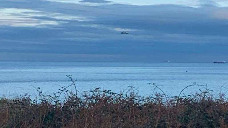 a flock of birds flying over a body of water: A multi-agency operation is under way at sea off the Anglesey coast following a report of an incident involving a light aircraft. Pic: @NWPanglesey