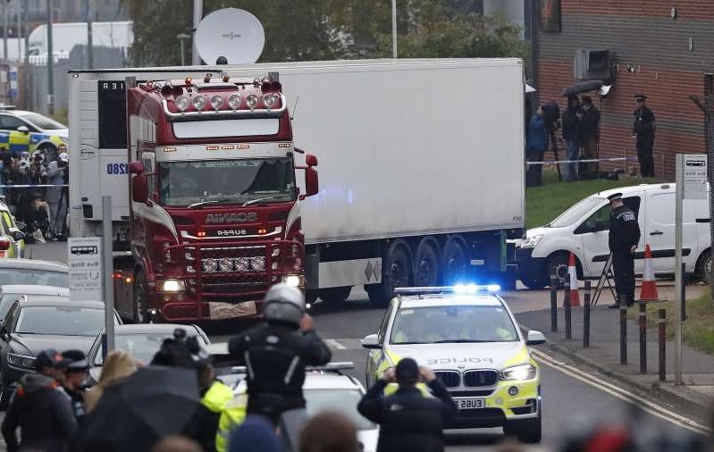 a group of police officers riding on the back of a truck: Maurice Robinson, the truck driver charged with manslaughter over the deaths of 39 Vietnamese migrants found in the back of a truck, pleaded guilty. Picture: AP Photo/Alastair Grant, File