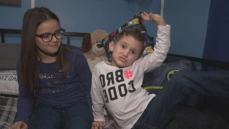 a person holding a baby: Jaxon Glazier (left) and his sister Savannah celebrate a room makeover courtesy of The Braedon Foundation, a charitable organization based in Saint John, N.B.