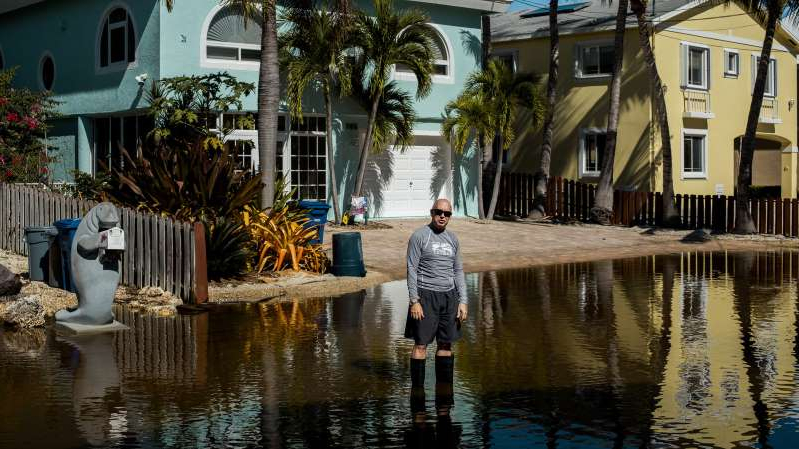 a person that is standing in the water: Bill Marlow, who lives in the Stillwright Point neighborhood in Key Largo, Fla., crossing the street in front of his house.