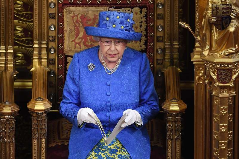 a person wearing a hat: The Queen reading the Queen's Speech at a reduced ceremonial state opening in 2017 (Carl Court/PA)