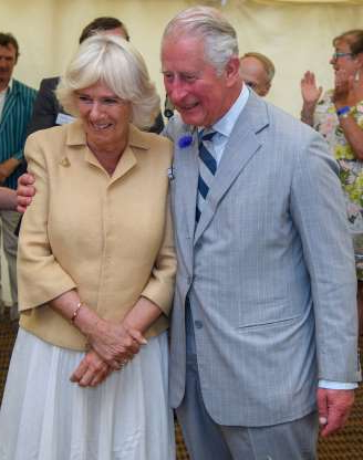 Slide 61 of 132: Prince Charles and wife Duchess Camilla shared a rare moment of PDA during the National Parks Big Picnic celebration in honor of all 15 of Britain's National Parks while visiting Simonsbath, England, on July 17.