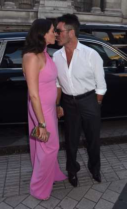 Slide 71 of 132: Simon Cowell and girlfriend Lauren Silverman kissed as they arrived at the SYCO summer party in London on July 4.