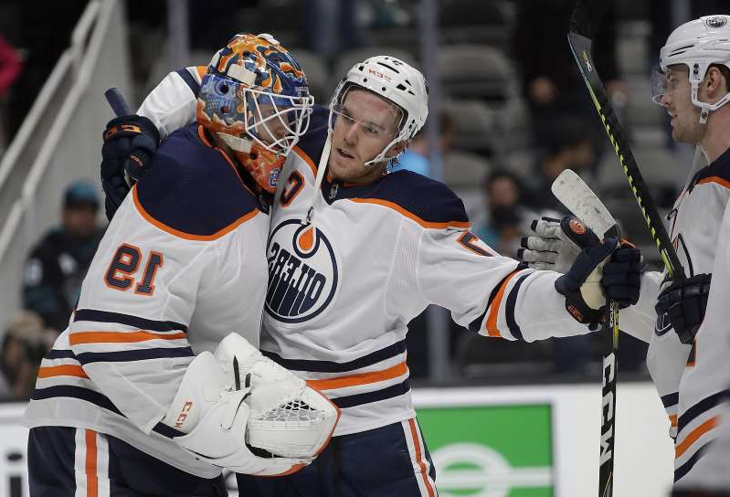 Connor McDavid et al. wearing costumes: Edmonton Oilers goalie Mikko Koskinen (19) celebrates with Connor McDavid at the end of an NHL hockey game against the San Jose Sharks on Tuesday, Nov. 19, 2019, in San Jose, Calif. (AP Photo/Ben Margot)