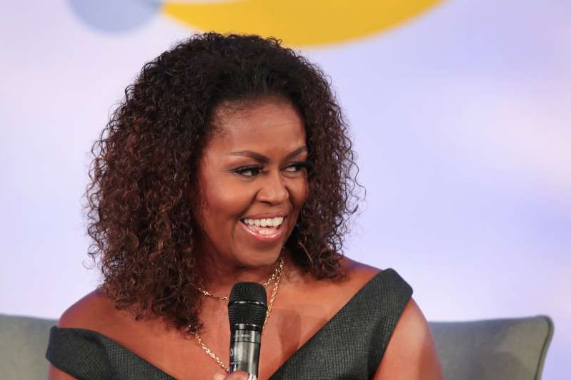 Michelle Obama wearing glasses and smiling at the camera: While Michelle Obama has often said she has no intention of running for president, Fox News host Tucker Carlson believes she will and that her husband Barack has not given his endorsement to leading Democratic candidate, former vice president Joe Biden.