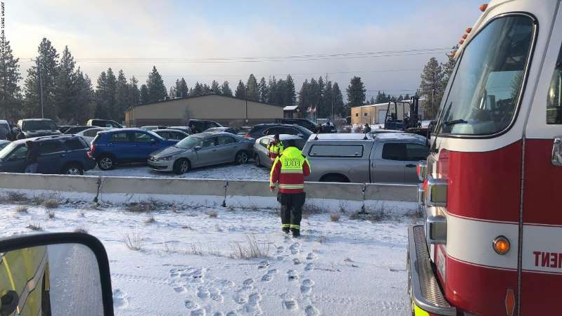 a car parked in a parking lot covered in snow: Interstate 90 near Spokane, Washington was completely shut down for several hours on Tuesday.