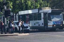 a group of people standing around a bus: A man was hit by a car on Royal Parade.