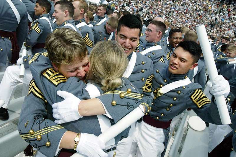 a group of people wearing military uniforms: U.S. Military Academy graduates embrace at the end of commencement exercises in 2003.
